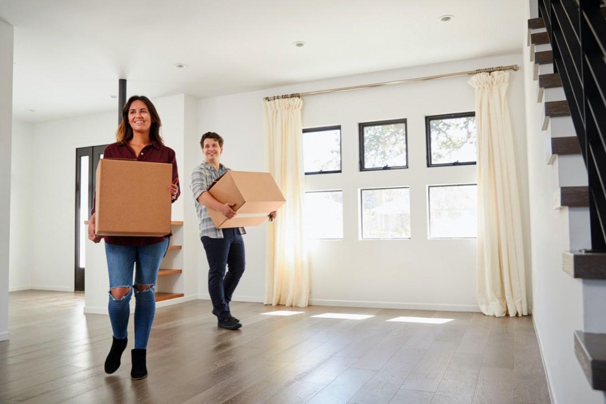 Glückliches Paar räumt neue Wohnung ein