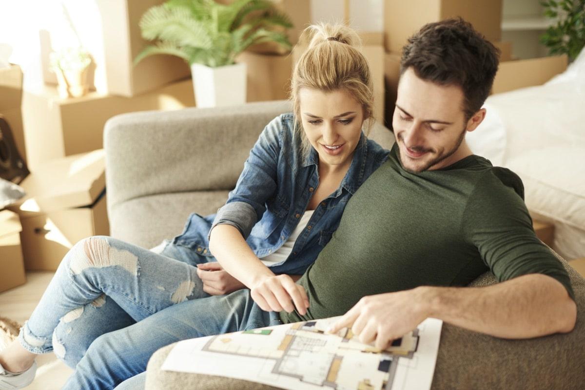 Paar plant Umzug auf dem Sofa mit Grundriss