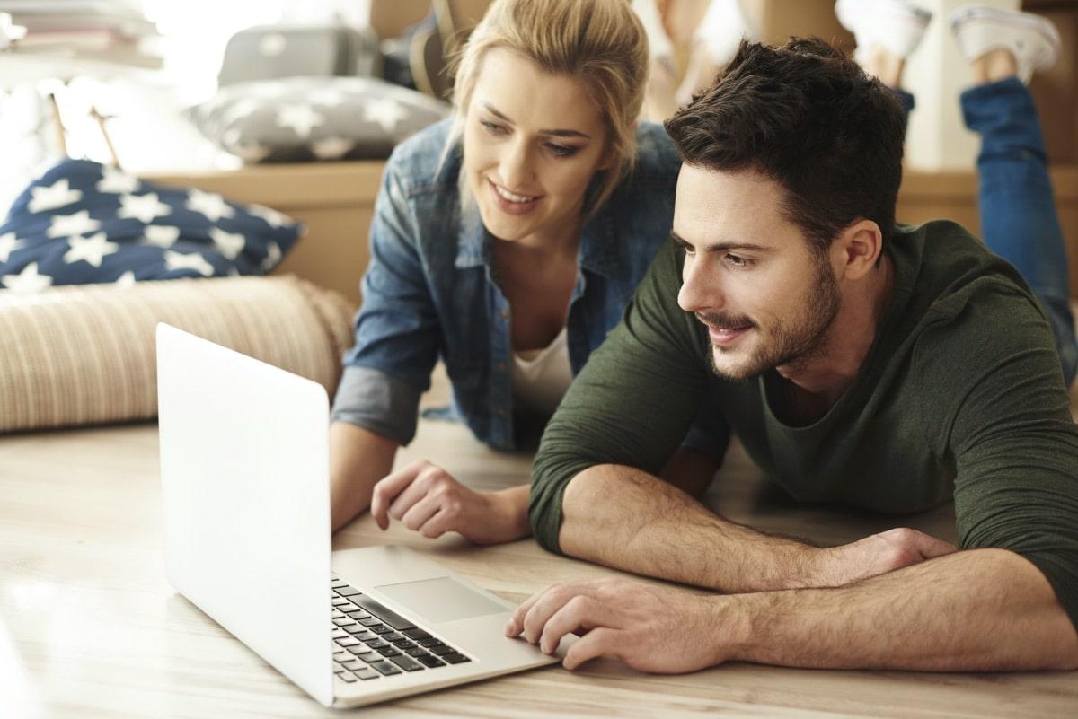 Paar plant Umzug am Laptop mit einer Checkliste für den Umzug